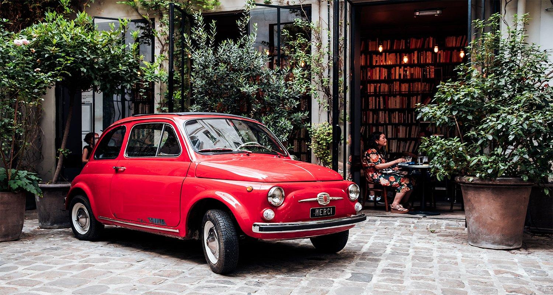 Fiat 500 rossa parcheggiata in un cortile