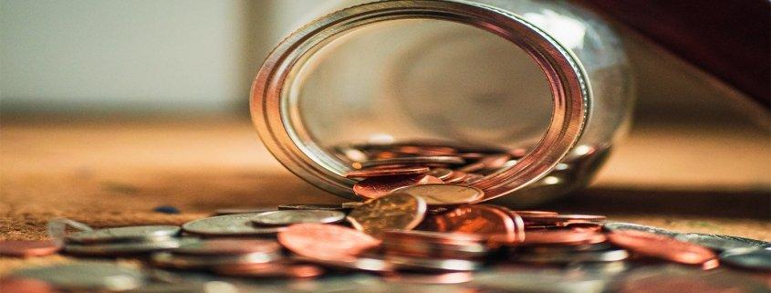 Salvadanaro aperto su tavolo e tante monete